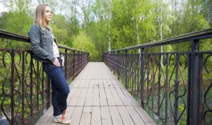 woman thinking whilst standing on a bridge