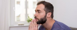 man staring into space with hands on face